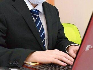 パソコンに向かうタケシさん。「まだまだ分からないことばかり」だが、日々の業務をこなしている=11月9日、那覇市樋川・どこでもワーク