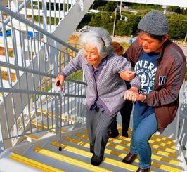 津波から逃れる訓練で、避難タワーの階段を上る久高島のお年寄りら=22日、南城市