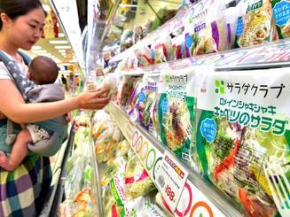 カット野菜商品を手に取る女性客=1日午後、サンエー那覇メインプレイス