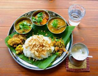 南インドカレー定食チキン&野菜。プレート上部のカレー3種は左からチキン、野菜、サンバル(野菜と豆のスープカレー)。右下のラッシーはカレーとセットで250円