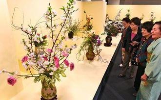 いけばなインターナショナル沖縄支部の展示会で、華やかな生け花の作品を鑑賞する来場者=25日午後、那覇市久茂地・タイムスビル