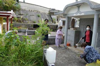 新型コロナウイルスの影響で、マスクをして墓掃除をする家族ら=25日、名護市大西の墓地