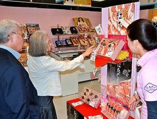県産豚のギフトコーナーで商品の品定めをする買い物客=27日、那覇市のデパートリウボウ