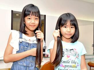 切った髪を手にする中村真彩さん(右)と津嘉山珠奈さん=23日、那覇市国場