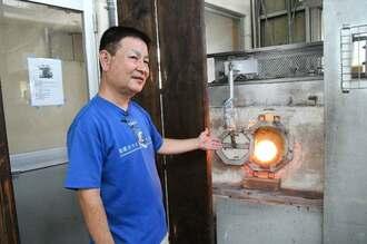 ガラスの原料を溶かす窯について説明する県琉球ガラス製造協同組合の松田英吉副理事長=10日、うるま市の琉球ガラス匠工房