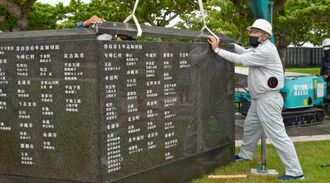 クレーンを使い、刻銘板を設置する作業員=17日、糸満市摩文仁の平和祈念公園