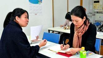 自分史講座で、講師の宜寿次政江さん(左)から書き方のアドバイスを受ける受講者=那覇市・桜坂劇場