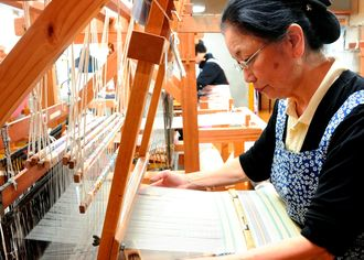 南風原花織を織る女性。浮き出る柄が華やかな印象を与える=日、南風原町・手織工房おおしろ