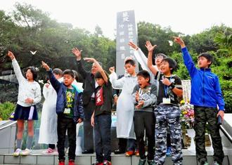 島守の塔で、平和の願いを込めたチョウ、オオゴマダラを放す神戸の子どもたち。上原昭糸満市長(中央奥)らも出迎えた=8日、糸満市摩文仁