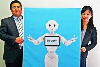 ペッパーを導入する沖銀の大城歩上席調査役(左)、島袋由香調査役=13日、沖縄タイムス社