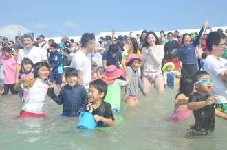 日本最南端の海開きで、一斉に海に入る参加者ら=18日午前10時半すぎ、竹富町小浜島・はいむるぶしビーチ