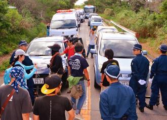 警察が抗議のプラカードを積んだ車(左手前)を行かせようとして途中で止めたため、2車線が詰まった=12日午前8時半すぎ、東村高江の県道70号