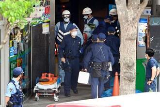 男が女性店員を人質に立てこもったインターネットカフェが入るビルに出入りする警察官や消防関係者ら=18日午後3時47分、さいたま市
