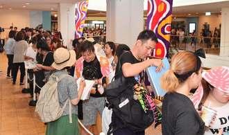 朝早くから入場を待つアムロファンで、長い行列ができた=2日午前、沖縄市・プラザハウス