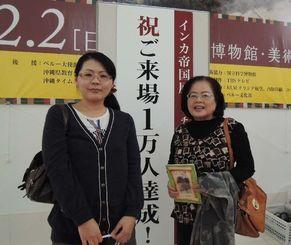 1万人目の来場者として記念品が贈られた宮里邦子さん(右)と歩美さん=那覇市の県立博物館・美術館