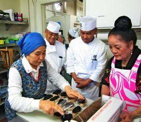 キッチンで調理指導に当たる山本さん(左)と補佐する上地さん(中央)=ガーデナ市の北米沖縄県人会館