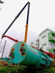基礎工事に使うハンマーをつり上げる作業中、アーム部分が折れて電線を切断したクレーン車=21日、宜野湾市大謝名
