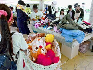 交換会には衣類やおもちゃが並び、多くの家族連れらが見入っていた=5日、豊見城市の美らSUNビーチ