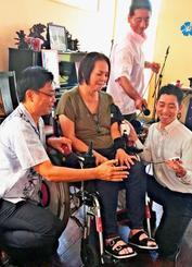 筋力を補助する装具「HAL」を使って、いつもとは違う指のスムーズな動きを実感する沖縄型原性筋萎縮症の女性(中央)=13日、沖縄市海邦・愛音楽(アネラ)はうす