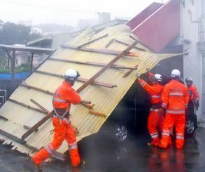 軽自動車の上に覆いかぶさる民家のトタン屋根=29日午後、沖縄市古謝