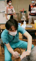 高齢者に新型コロナウイルスワクチンを接種する大和市立病院歯科口腔外科の小沢知倫科長=18日午前、神奈川県大和市