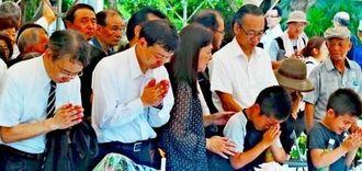 ひめゆりの塔の慰霊祭に初めて参列し、手を合わせる故野田貞雄校長の孫の(左から)雅生さん、英樹さん。中央奥の白いシャツが、謙二さん=糸満市伊原