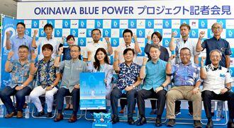 「ブルーリストバンド」を着けてポーズを取る「オキナワブルーパワープロジェクト」の実行委員会メンバーら=12日、那覇市のパレットくもじ前イベント広場