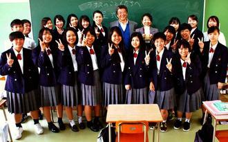 ラオスの子どもたちに授業で得た利益を寄付した具志川商業高校の生徒ら=22日、うるま市の同校