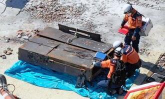 全焼した正殿の北側から運び出した「電灯盤」とみられる大型の電気系統設備を調べる消防隊員ら=6日午後0時17分、那覇市首里当蔵町(小型無人機で撮影)