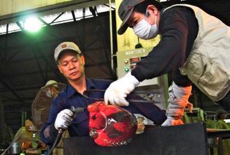 琉球ガラス村の職人(右)から技術指導を受けるベトナム人スタッフ(提供)=ベトナム・ハノイ市