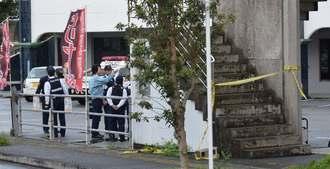 強盗が押し入ったインターネットカフェ周辺を警戒する警察官ら=19日午前7時15分ごろ、沖縄市中央