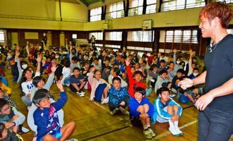 マジックのパートナーをしたい人と呼び掛けるMASAさん(右)と手を挙げる児童=17日、浦添市立港川小学校