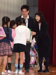 児童書や絵本を寄贈し、「そよかぜ文庫」をつくった屋宜奏花さんの(右から)母道代さん、父司さん=13日、宜野湾小学校