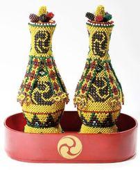1870年に尚泰王から伊是名島の銘苅家に贈られた一対の「黄色地巴紋御玉貫(きいろじともえもんうたますき)」と、朱漆の置盆