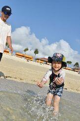 晴天の下、ビーチで遊ぶ親子=13日午後4時45分、豊見城市豊崎の「オリオンECO 美らSUNビーチ」(小宮健撮影)