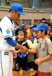 嶺井博希捕手(左)から帽子を受け取り、握手する児童=宜野湾市立体育館