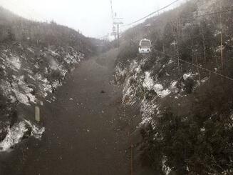 23日午前にスキー場のゴンドラから乗客が撮影した、噴火した本白根山の降灰などに覆われて黒くなった雪面=群馬県草津町