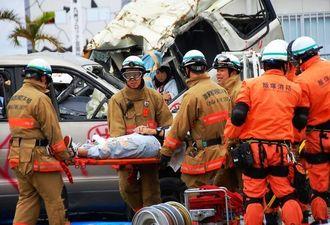 押しつぶされた車両から住民の救助訓練を行う消防士ら=28日、与那原町