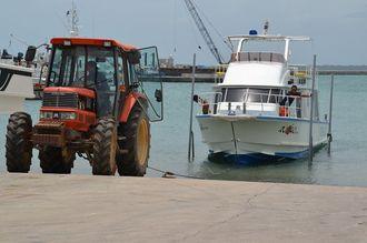漁船を陸揚げする漁師ら=6日午後0時半45分ごろ、石垣港