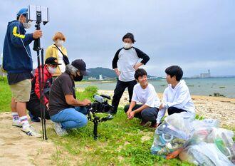 CMの撮影に臨む古謝真南斗さん(右端)と伊野波有志さん(右から2人目)=4月4日、中城村内