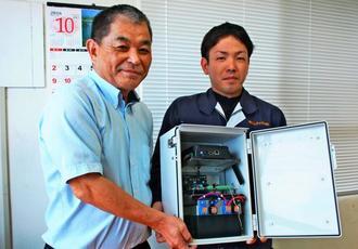 小型化、低価格を実現したテレメーターを紹介する大城豊代表(左)と開発担当の吉本武徳氏=24日、那覇市・コムテック創研