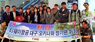 ミス沖縄コバルトブルーの町田満彩智さん(上段右端)らに迎えられたティーウェイ航空の乗客=2日、那覇空港国際線ビル