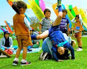 手作りこいのぼりの周りで遊ぶ子どもたち=26日、糸満市・平和祈念公園(金城健太撮影)