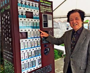 しまくとぅばグッズの自販機の前で、新たな継承保存の必要性を語るしまくとぅば連絡協議会の池原稔会長=日、嘉手納町