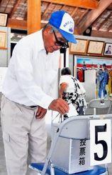 繰り上げ投票で1票を投じる有権者ら=4日午後、竹富町・竹富島まちなみ館