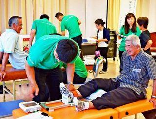 下肢の筋力を測定した参加者ら=16日、沖縄赤十字病院