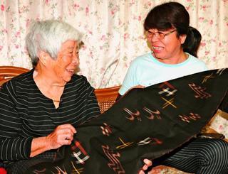 久米島紬の「どぅるくゎーしー(泥染め)」について語った宮平登美子さん(左)と、次女の佐久田美佐子さん。第一人者とされる母の泥染めをこの秋は手伝い、習う=13日、久米島町