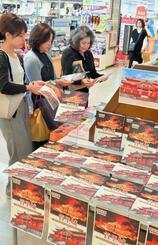 平積みされた「報道写真集 首里城」を手にする来店客=14日、那覇市・ジュンク堂書店那覇店