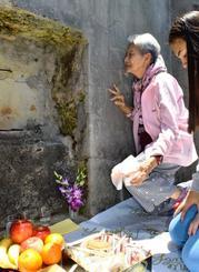 門中墓に身を寄せ、亡き父への思いをはせる冨里ゼナイダスミコさん=26日、うるま市・津堅島