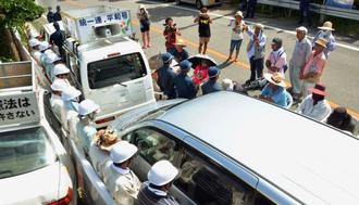 市民が止めた車列の間に立つ防衛局職員(左側)=日、東村高江・N1地区ゲート(記事中の職員とは関係ありません)